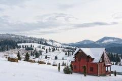Häuschen in den schneebedeckten Hügeln von Siebenbürgen Lizenzfreie Stockfotos