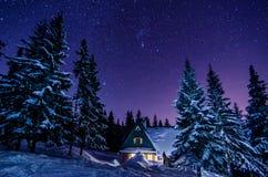 Häuschen des Berges Milchstraßegalaxie Purpurrote Sterne des nächtlichen Himmels über Bergen Lizenzfreie Stockfotografie
