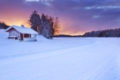 Häuschen entlang einem gefrorenen See im Winter, Levi, finnisches Lappland Stockfotografie