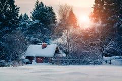 Häuschen mit Rauche im feenhaften Wald des Winters Stockfotos
