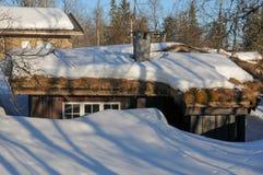 Häuschen mit Schnee auf dem Dach Stockbilder