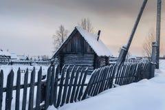 Häuschen am schneebedeckten Morgen des Dorfs eins in Russland Stockfotografie