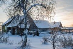 Häuschen am schneebedeckten Morgen des Dorfs eins in Russland Stockbild