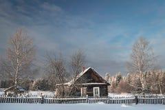Häuschen am schneebedeckten Morgen des Dorfs eins in Russland Lizenzfreie Stockfotos