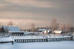 Häuschen am schneebedeckten Morgen des Dorfs eins in Russland Lizenzfreies Stockfoto