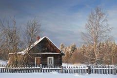 Häuschen am schneebedeckten Morgen des Dorfs eins in Russland Lizenzfreies Stockbild