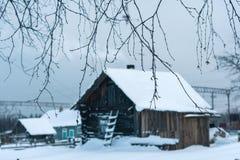 Häuschen am schneebedeckten Morgen des Dorfs eins in Russland Lizenzfreie Stockbilder