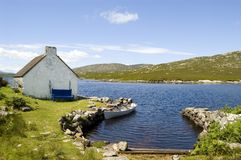 Häuschen und Boot in Connemara lizenzfreie stockfotografie