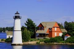 Häuschen und Leuchtturm des hölzernen Hauses auf dem Fluss Lizenzfreie Stockfotos