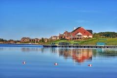 Häuser auf Ufer von blauem See Lizenzfreie Stockfotos