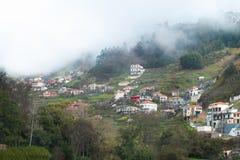 Häuser in den Bergen inmitten eines Waldes und eines dichten Nebels Stockbilder
