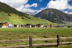 Häuser in der Bergwiese hinter Zaun Lizenzfreies Stockbild