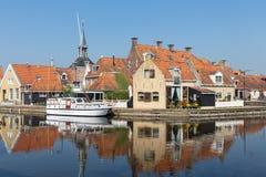 Häuser entlang einem Kanal in Makkum, ein altes niederländisches Dorf stockfotografie