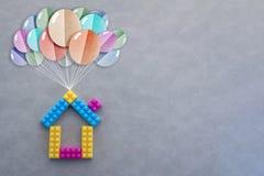 Häuser mit den Ballonen, die durch den Himmel schwimmen Stockfoto