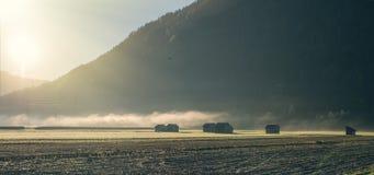 Häuser in Nebel der Schweiz morgens gegen den Hintergrund der Berge Landschaft eines Schweizer Dunstes des Dorfs morgens Lizenzfreie Stockfotografie