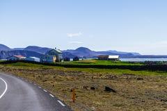 Häuser und eine Straße entlang dem Feld in Island stockbild