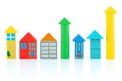 Häuser und Türme builded von den bunten Holzklötzen, die auf weißem Hintergrund mit Schattenreflexion lokalisiert wurden Lizenzfreies Stockfoto