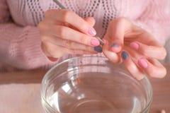 Häutchen-Entferner Frau macht Maniküre selbst Nahaufnahmehände stockbilder