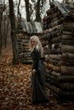 Häxa i en lång svart klänning royaltyfri bild