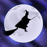 Häxa på en kvastskaft som flyger den halloween feriemånen i den stjärnklara himlen Royaltyfria Foton