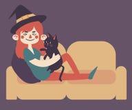 Häxa på soffan med katten Royaltyfria Bilder