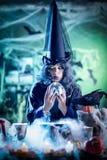 Häxa som håller ögonen på framtiden i magisk boll royaltyfri fotografi