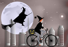 Häxa som rider en cykel runt om staden och häxaflyget på en kvast över staden i beröm av allhelgonaaftonen Royaltyfria Foton