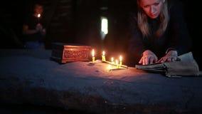 Häxa som rymmer den magiska ritualen gammalt bokstearinljus halloween stock video