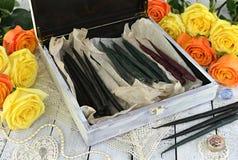 Häxaask med svarta stearinljus, garneringar och gula rosor på plankor Arkivbild