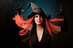Häxan öva witchcraft på svart bakgrund. Arkivbilder
