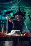 Häxan berättar magiska ord till skallen royaltyfri bild
