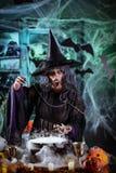 Häxan lagar mat magisk dryck med ben royaltyfria foton