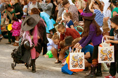 Häxan räcker godisen till ungar på Halloween ståtar ut Royaltyfri Foto