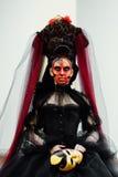 Häxastående i svart tappningklänning Kvinnaänka med det röda konstsminket för halloween Arkivbild