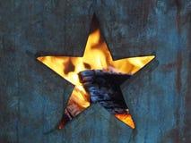Hål i formen av ettpekat stjärnasnitt in i en metallbränningtrumma med flammor och den brända synliga insidan för trä arkivbild
