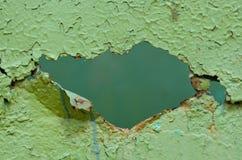 Hål i gammal grön metallvägg Royaltyfria Foton