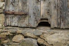 Hål i gammal ladugårddörr arkivfoton