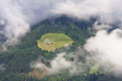 Hål i moln i österrikiska berg Arkivfoton