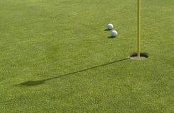 Hål och golfbollar i greenback Arkivfoton