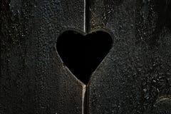 Hål på ett wood fönster med hjärtaform Arkivfoton