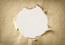Hål som göras av sönderrivet papper över texturerad kanfasbakgrund Arkivfoton