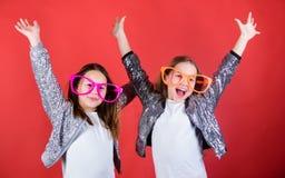Håll att fira Kalla partiflickor som bär utsmyckade exponeringsglas Små ungar i partiskyddsglasögon som har gyckel deltagare för  royaltyfri bild