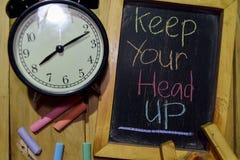 Håll ditt huvud upp på färgrikt handskrivet för uttryck på den svart tavlan arkivfoton