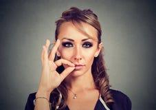 Håll en hemlig ung kvinna som drar igen blixtlåset på hennes stängda mun Tyst begrepp Royaltyfri Fotografi