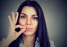 Håll en hemlighet, kvinnan som drar igen blixtlåset på hennes stängda mun Tyst begrepp Fotografering för Bildbyråer