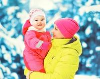 Håll för moder för vinterstående behandla som ett barn lyckliga le på hennes händer över snöig julträd Arkivfoto