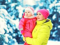 Håll för moder för vinterstående behandla som ett barn lyckliga på händer över snöig julträd Royaltyfria Bilder