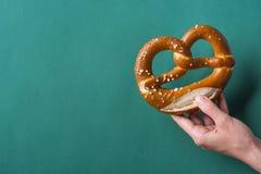 Håll för ung kvinna i tysk välsmakande lutkringla för hand med salt på mörker - grön bakgrund Affischbaner för bagericoffee shopm royaltyfria foton