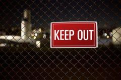 Håll varnande det ut tecknet på ett chainlinkstaket under natten som bevakar den privata egenskapen Arkivfoto