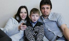 hålla ögonen på för tv Den unga den familjmamman, farsan och sonen håller ögonen på TV tillsammans Arkivfoto